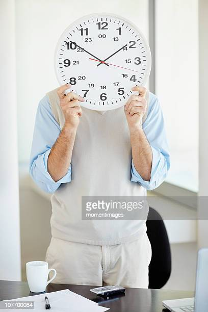 South Africa, Office worker holding clock in front of face