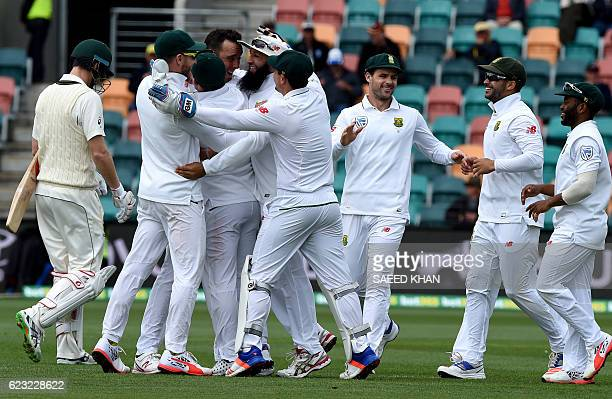 South Africa paceman Kyle Abbott celebrates his wicket of Australia's batsman Adam Voges with teammates on the fourth day's play of the second Test...