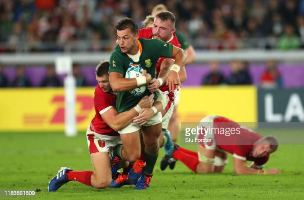 South Africa player Handre Pollard is tackled by Dan Biggar and Dillon Lewis during the Rugby World Cup 2019 SemiFinal match between Wales and South...