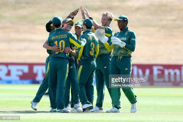 South Africa players celebrate the dismissal of Mohammed Naim Sheikh of Bangladesh during the ICC U19 Cricket World Cup 5th Playoff match between...