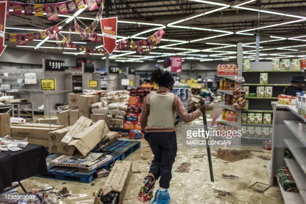 South Africa police officer inspects the damages at a looted mall in Vosloorus, on July 13, 2021. - Stores in two South African provinces were...
