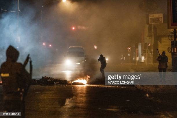 South Africa Police Service officer aims his rifle at a in incoming minivan bringing it to a stop in Jeppestown, Johannesburg, on July 12, 2021...