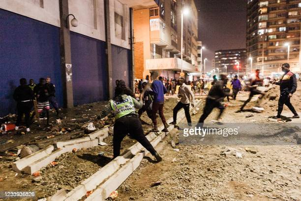 South Africa Police Services officers stop looters from looting in central Durban, on July 11, 2021. - Several shops are damaged and cars burnt in...