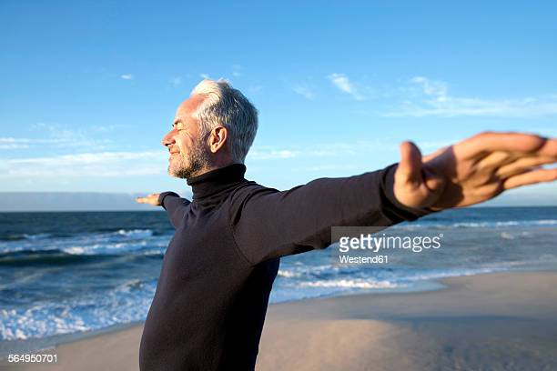 South Africa, portrait of man wearing turtleneck standing on beach dunes with outstretched arms before sunrise