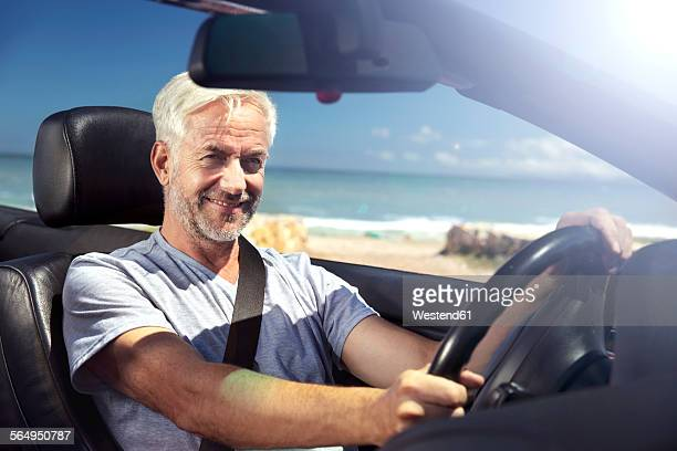 South Africa, portrait of smiling man sitting in a convertible in front of the beach