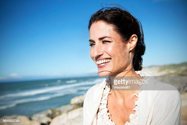 South Africa, portrait of smiling woman looking at the sea