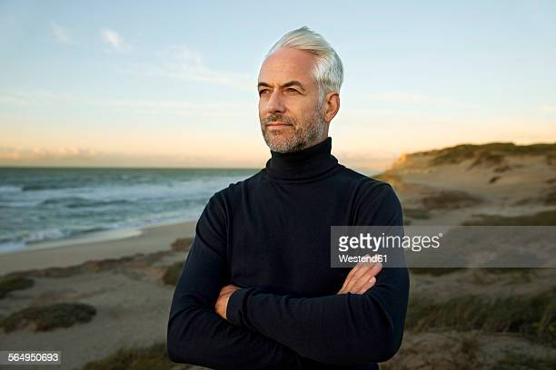 South Africa, portrait of white haired man wearing turtleneck standing on beach dunes before sunrise