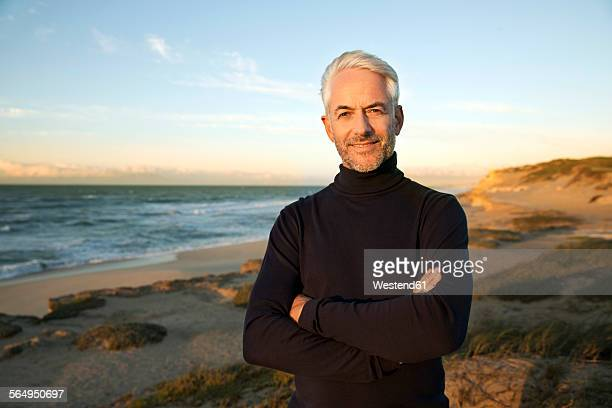 south africa, portrait of white haired man wearing turtleneck standing on beach dunes before sunrise - polo neck stock pictures, royalty-free photos & images