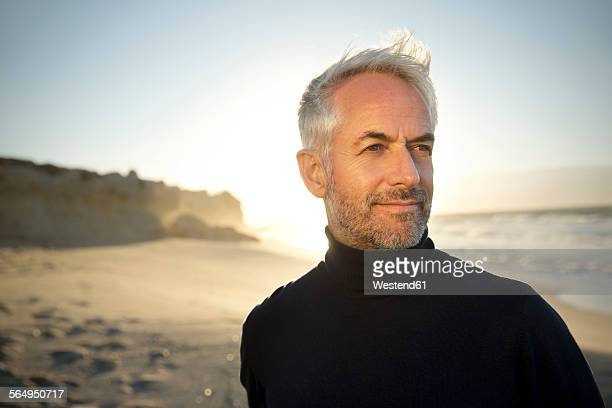 South Africa, portrait of white haired man wearing turtleneck standing on the beach before sunrise