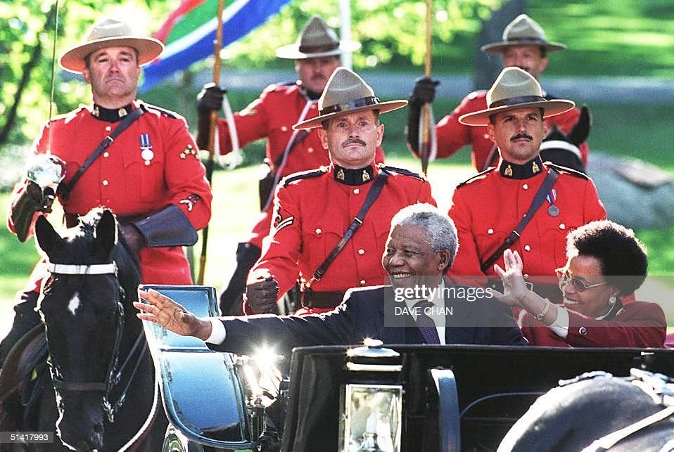 South Africa President Nelson Mandela (L front) and his wife Graca Machel (R front) waves to the crowd during a welcoming ceremony at Rideau Hall in Ottawa, Canada, 23 September. Mandela is on a three day state visit to Canada. AFP PHOTO Dave CHAN