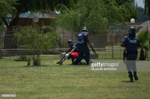 South Africa riot police officers detain a man during clashes with protesters including disgruntled parents South African ruling Party African...
