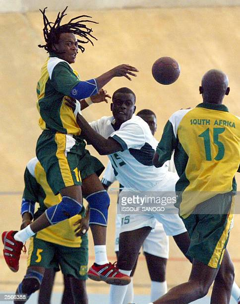 South Africa 's Pekile Victor jumps to collect the ball as Senegalese defenders rush in as part of the handball match opposing South Africa vs...