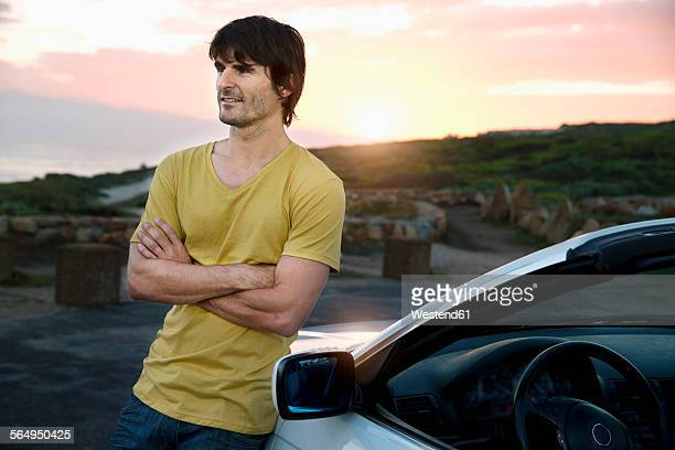 South Africa, smiling man at parked car at sunrise