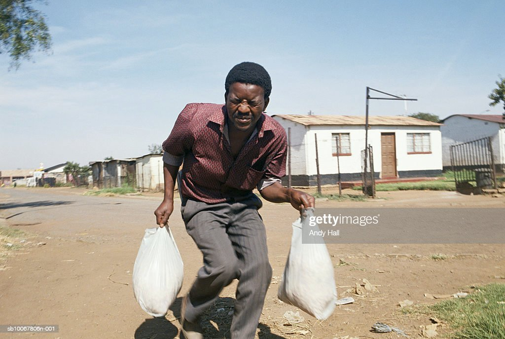 South Africa, Tokoza, young man running with shopping during shootout : Foto di attualità