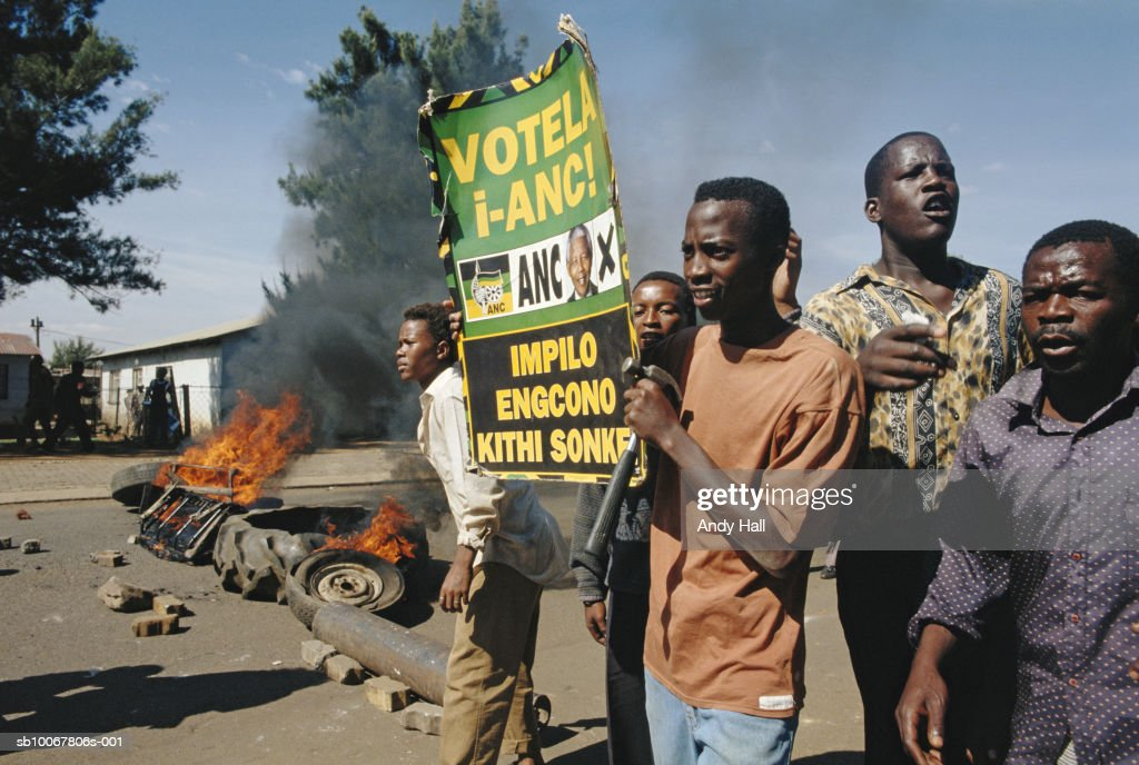 South Africa, Tokoza, group of men with placard, car burning in background : Foto di attualità