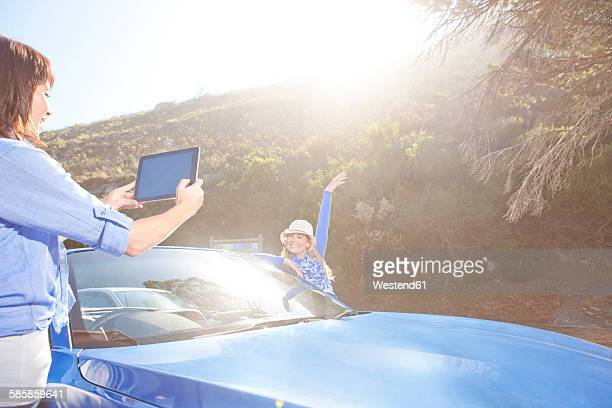 South Africa, two happy women at a convertible taking pictures with a digital tablet