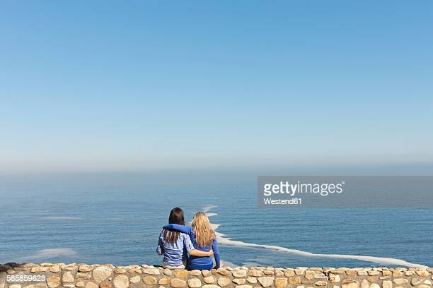South Africa, two women sitting arm in arm on a wall at the coast