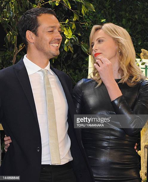 South African actress Charlize Theron and director Rupert Sanders pose for photographers during a press event to promote their latest movie 'Snow...