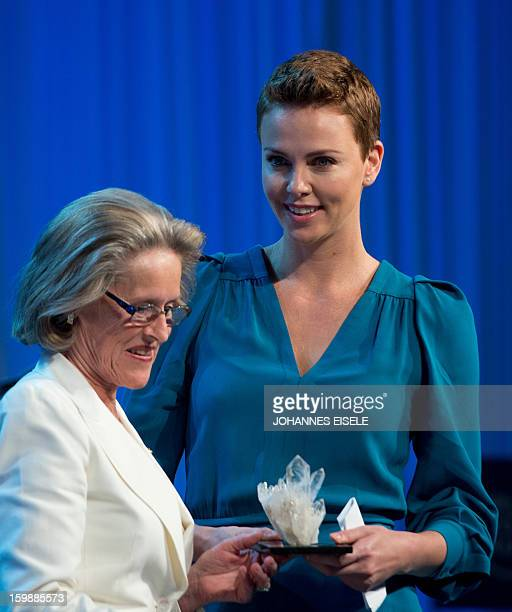 South African actress Charlize Theron receives an award from Hilde Schwab wife of chairman Klaus Schwab at the presentation of the Crystal Award...