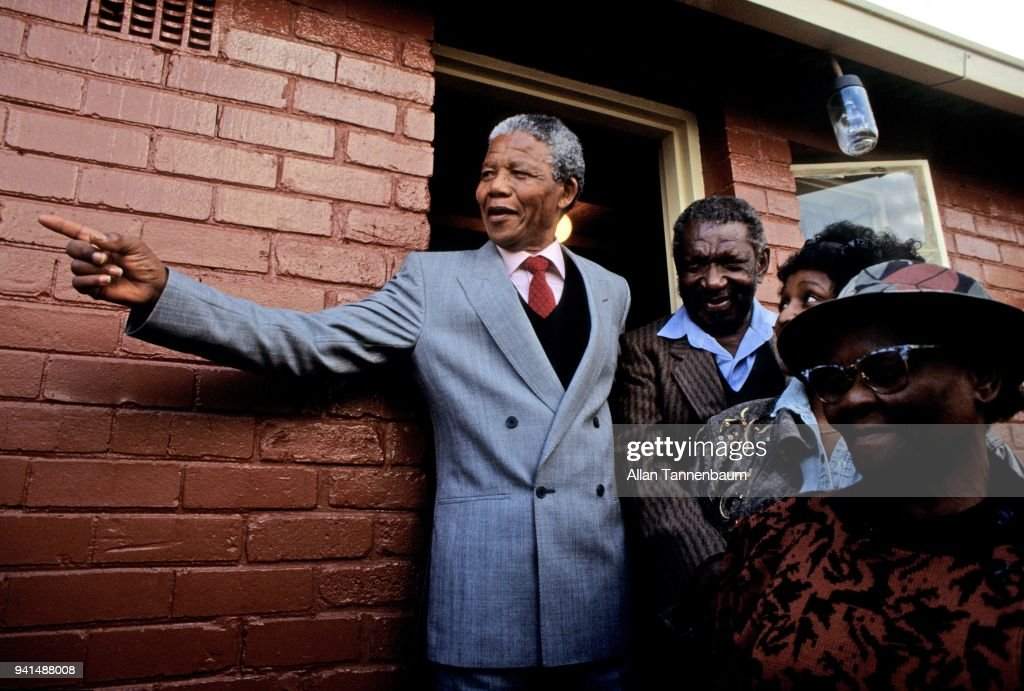 South African anti-apartheid activist (and future President) Nelson Mandela (1918 - 2013) points outside the door of his home, Soweto, Johannesburg, South Africa, February 15, 1990. He had been released from prison four days previously. With him are several friends, and his wife and fellow activist, Winnie Mandela (1936? - 2018) (second right).