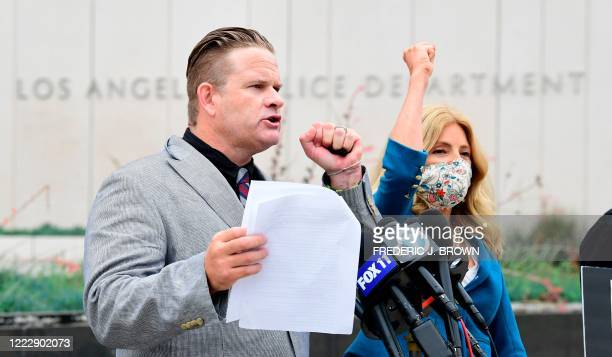 South African anti-apartheid activist/author Bradley Steyn and attorney Lisa Bloom gesture with their fists during a press conference outside the Los...