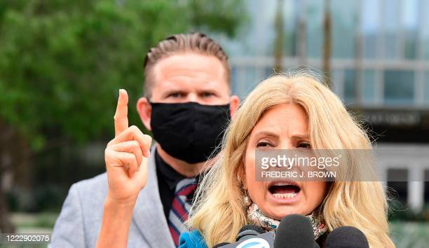 South African anti-apartheid activist/author Bradley Steyn looks on as attorney Lisa Bloom gestures mimicking the firing of a gun during apress...