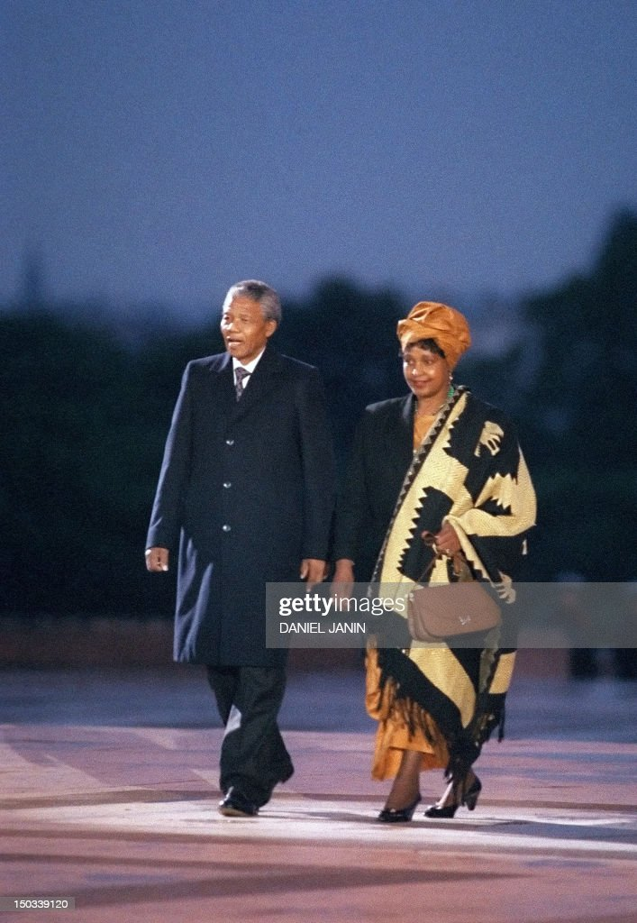 South African anti-apartheid leader and African National Congress (ANC) member Nelson Mandela (L), flanked by his wife anti-apartheid campaigner Winnie (R), attends a ceremony in his honour at Trocadero Square on the Plaza of Freedom and Human right, 06 June 1990 in Paris. Nelson Mandela, who was released from jail on 11 February 1990, is in Paris for a two-day official visit. / AFP PHOTO / Daniel JANIN