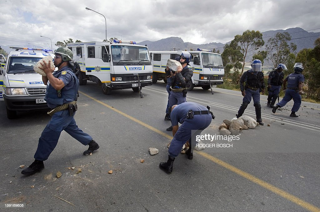 South African anti-riot Police clear rocks off the N1 National Road after clashes broke out on January 9, 2013 striking farm workers in De Doorns, a small farming town about 140km north of Cape Town, South Africa. Workers on fruit farms have downed tools, demanding a wage hike from 69 rand ($8) to 150 rand ($17.50) a day. The protesters also occupied part of the country's major N1 highway, forcing dozens of police officers and two armoured vehicles to move down the road, pushing the protesters back from the town entrance.