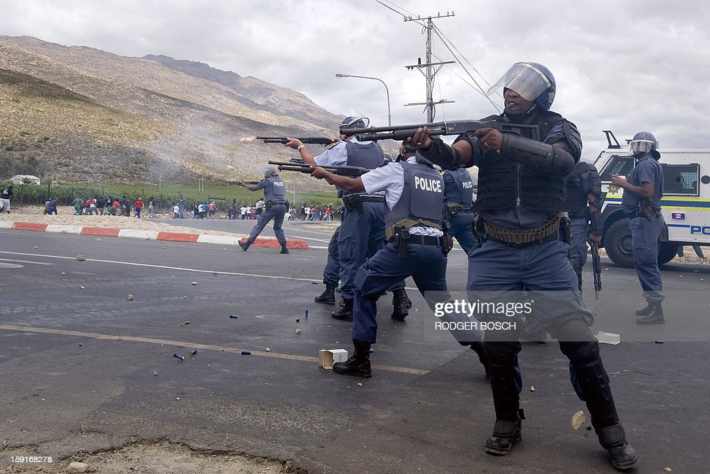 South African anti-riot Police fire rubber bullets at striking farm workers after clashes broke out on January 9, 2013 in De Doorns, a small farming town about 140km north of Cape Town, South Africa. Workers on fruit farms have downed tools, demanding a wage hike from 69 rand ($8) to 150 rand ($17.50) a day. The protesters also occupied part of the country's major N1 highway, forcing dozens of police officers and two armoured vehicles to move down the road, pushing the protesters back from the town entrance.
