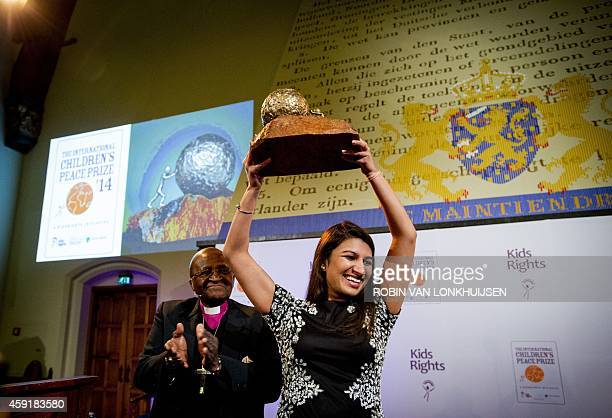 South African Archbishop Desmond Tutu applauds on November 18, 2014 as American Neha Gupta receives the 10th International Childrens Peace Prize in...