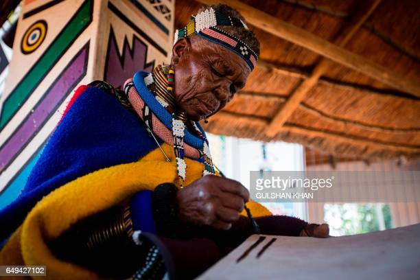 South African artist Esther Mahlangu paints at her home in Mabhoko Village Siyabuswa Mpumalanga on March 6 2017 Mahlangu recently opened her...