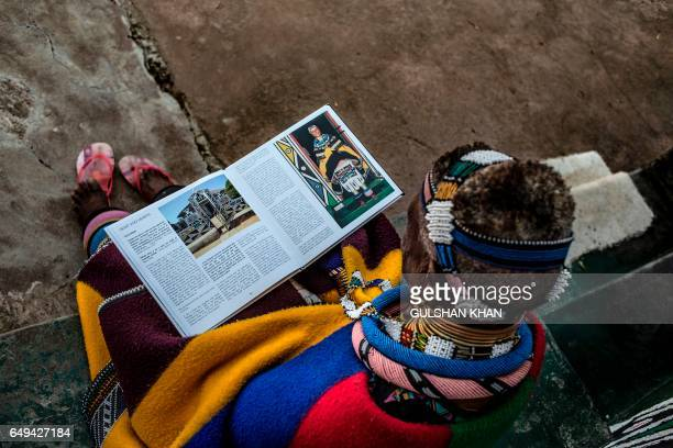 South African artist Esther Mahlangu read a biography of work at her home in Mabhoko Village Siyabuswa Mpumalanga on March 6 2017 Mahlangu recently...