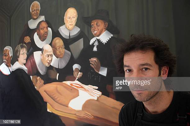 South African artist Yuill Damaso poses next to his controversial painting that depicts South Africa's first Black president Nelson Mandela lying on...