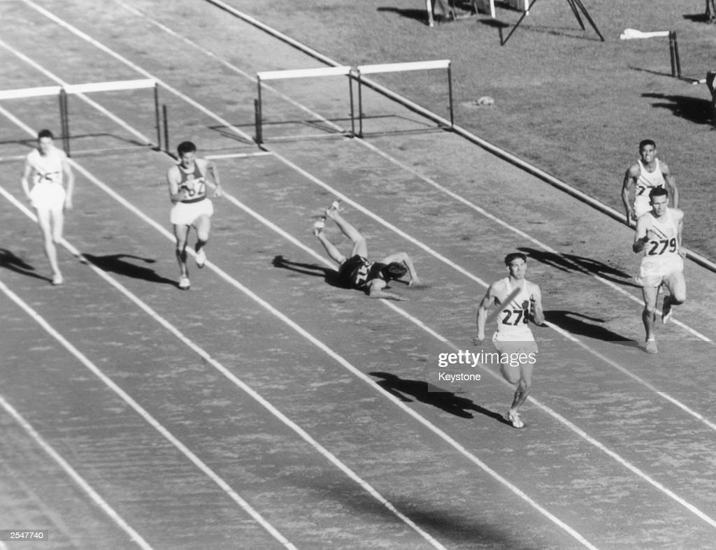 South African athlete Gerhardus Potgieter trips up at the last hurdle during the final of the 400 metres hurdles during the Olympic Games, Melbourne, Australia, 29th November 1956. The race was won by American Glenn Davis (No. 278), with Silas Southern (No. 279) second and Joshua Culbreath (No. 277) third.