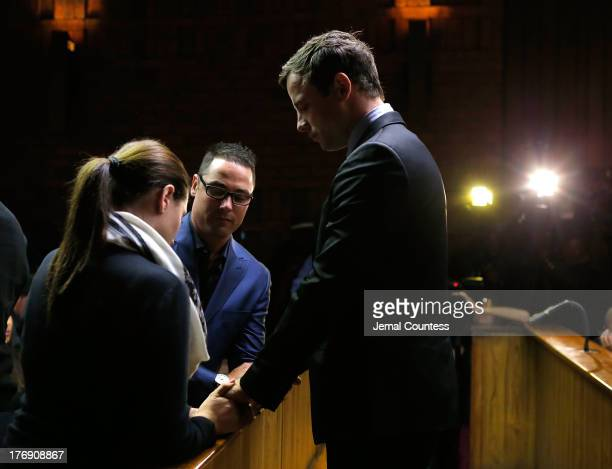 South African athlete Oscar Pistorius prays with his brother Carl Pistorius and his sister Aimee Pistorius prior to his indictment hearing in...
