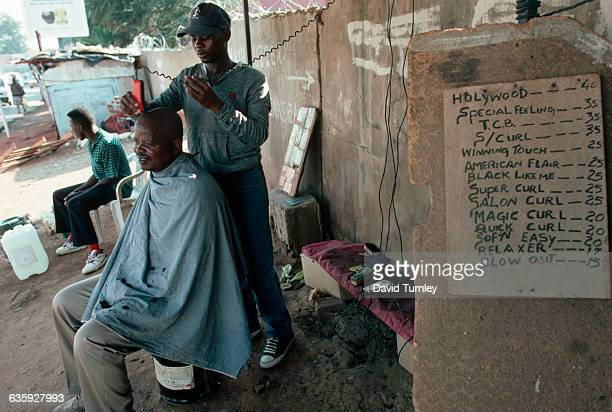 A South African barber shaves a man's head with clippers as another customer waits along a street in Alexandra Township