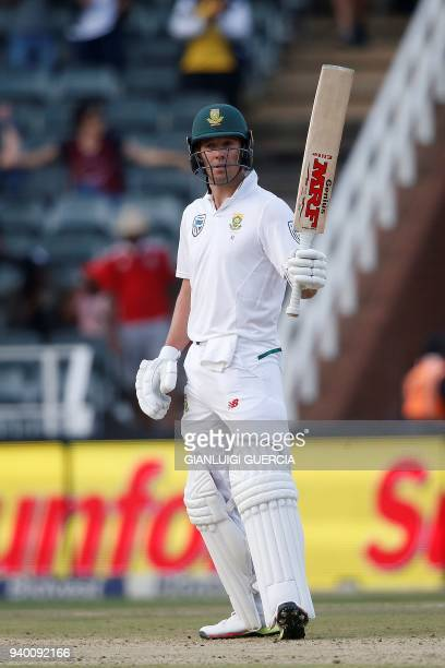 South African batsman AB de Villiers raises his bat as he celebrates scoring half century on the first day of the fourth Test cricket match between...