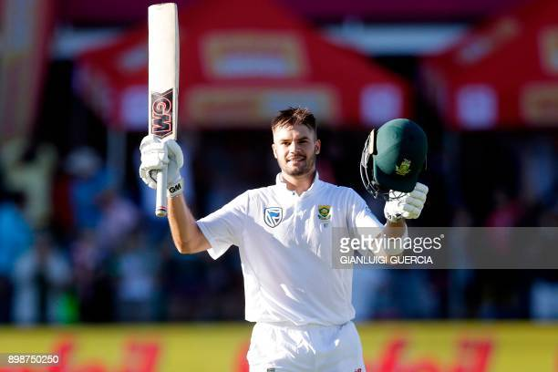 South African batsman Aiden Markram raises his bat and helmet as he celebrates after scoring a century during the first day of the day night Test...