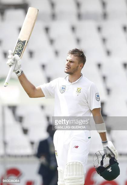 South African batsman Aiden Markram raises his bat and helmet as he celebrates scoring a century during the first day of the fourth Test cricket...