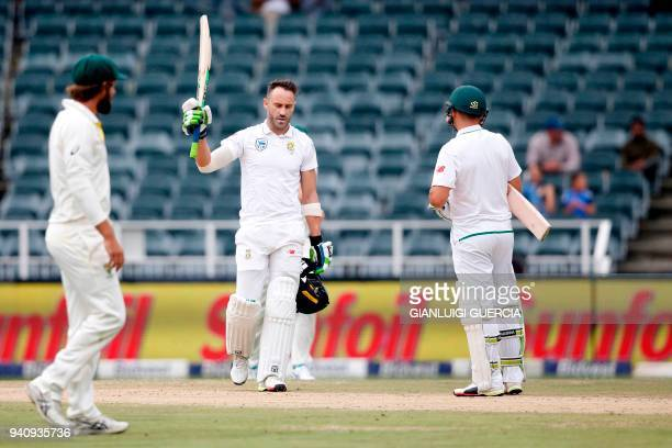 South African batsman and Captain Faf du Plessis raises his bat as he celebrates scoring a century on the fourth day of the fourth Test cricket match...