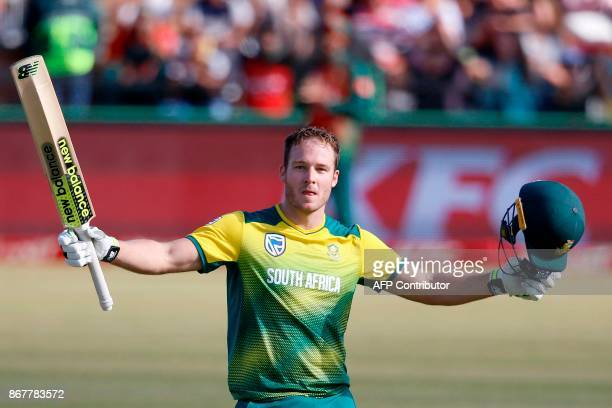 South African batsman David Miller raises his bat and helmet as he celebrates scoring a century during the second T20 cricket match between South...