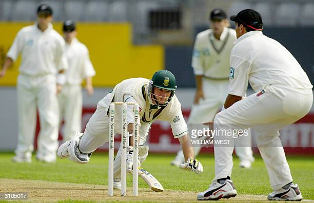 South African batsman Graeme Smith dives for his crease as New Zealand fieldsman Daryl Tuffey attempts to run him out on the first day of the second...