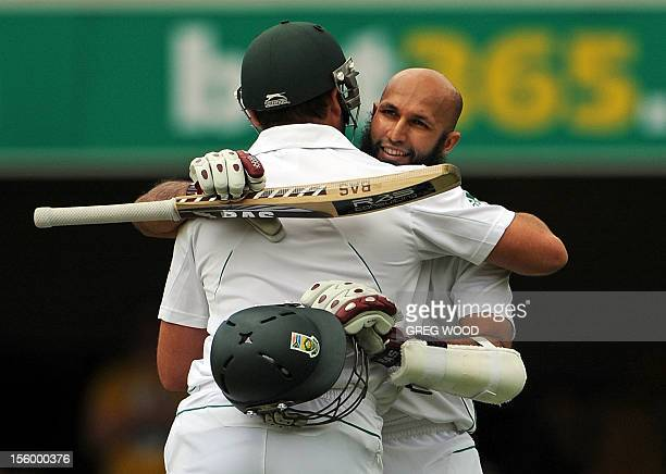 South African batsman Hashim Amla is congratulated by teammate Jacques Kallis after reaching his century on day three of the first cricket Test...
