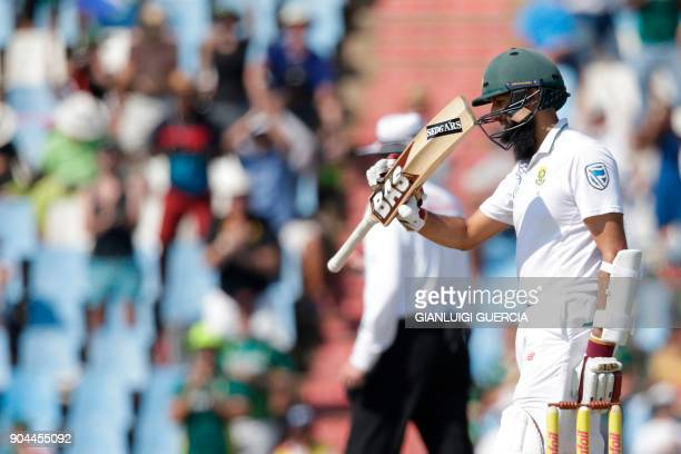 South African batsman Hashim Amla lifts his bat as he celebrates scoring a halfcentury during the first day of the second Test cricket match between...