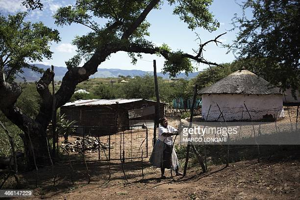 South African Bhekekile Ndlovu her face traditionally painted with clay closes the gate to her parcel of land directly opposite the lavish residence...
