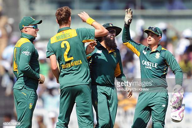 South African bowler Chris Morris celebrates with his teammates after the dismissal of Indian batsman Rohit Sharma during the fourth one day...