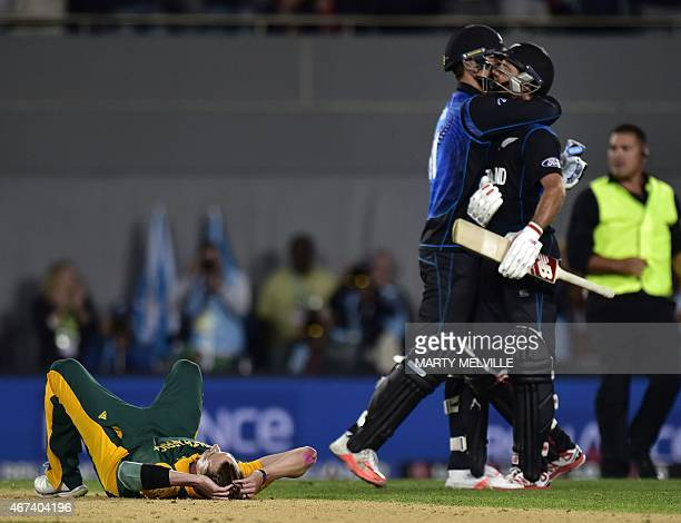 South African bowler Dale Steyn sits dejected after his team's loss as New Zealand batsman Grant Elliott and Daniel Vettori celebrate during the...
