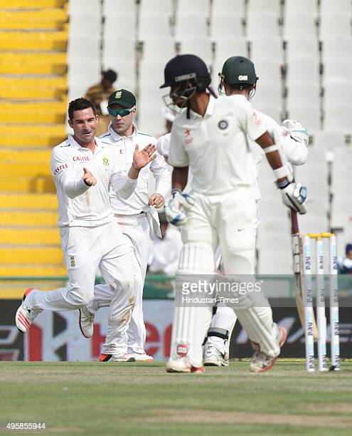South African bowler Dean Elgar celebrates after taking the wicket of Indian batsman Wriddhiman Saha during the first test match at PCA Stadium on...