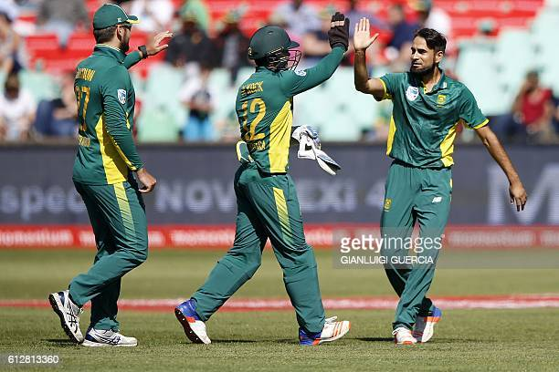 South African bowler Imran Tahir celebrates with teammates the dismissal of Australian batsman Aaron Finch during the third One Day International...