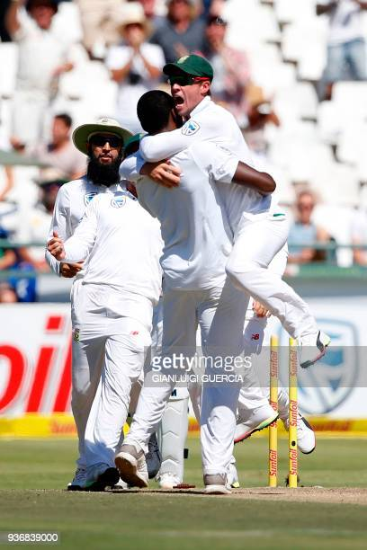 South African bowler Kagiso Rabada and fielder AB de Villiers celebrates the dismissal of Australian batsman David Warner during the second day of...